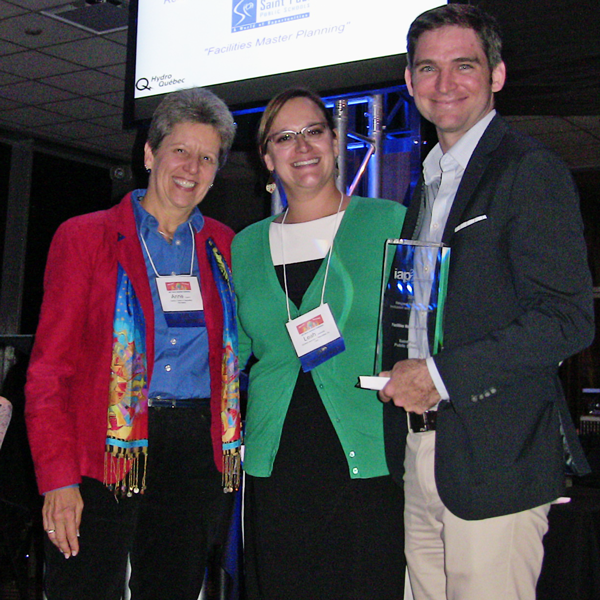 Former School Board member Anne Carroll and Facilities Director Tom Parent of Saint Paul Public Schools receive the award for Respect for Diversity, Inclusion and Culture from IAP2 USA President Leah Jaramillo